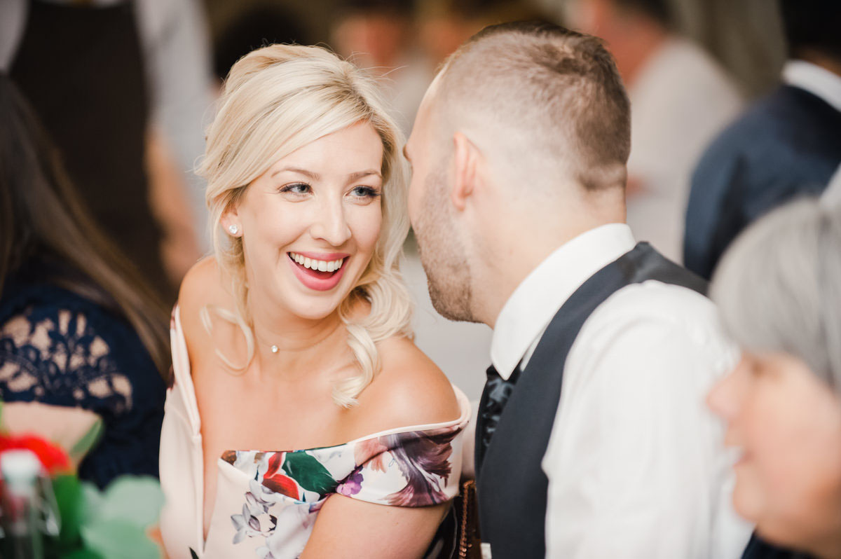 Wedding photo of a woman with blonde hair and a floral dress looking at her male partner and laughing at a wedding reception
