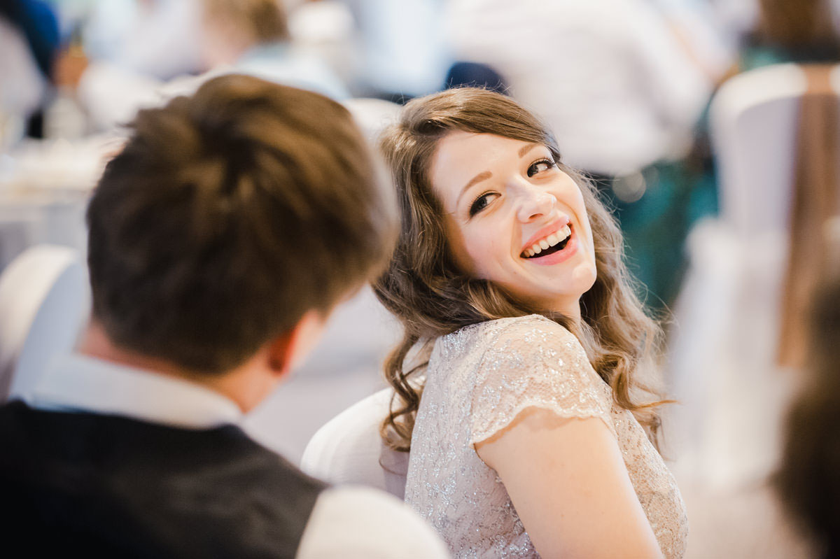 Wedding photograph of a bride with curly brown hair laughing, with her head turned to face her groom during wedding speeches