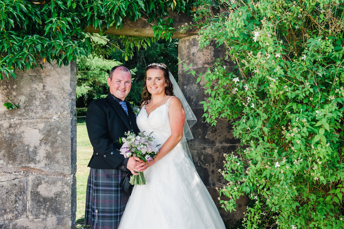 Outdoor wedding photo of a bride and groom standing in the doorway of a stone wall with a large green bush on one side