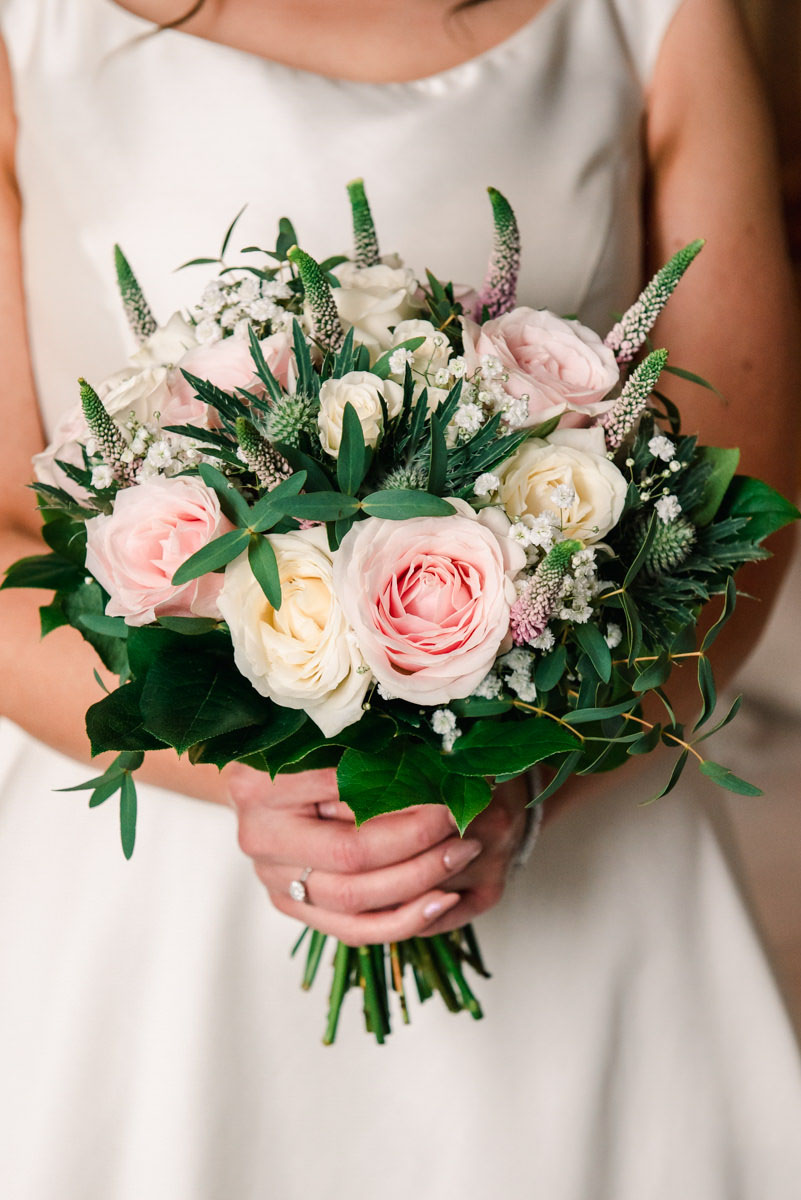 A close-up image of a bouquet of pink and cream roses, being held by a bride wearing a simple white wedding dress