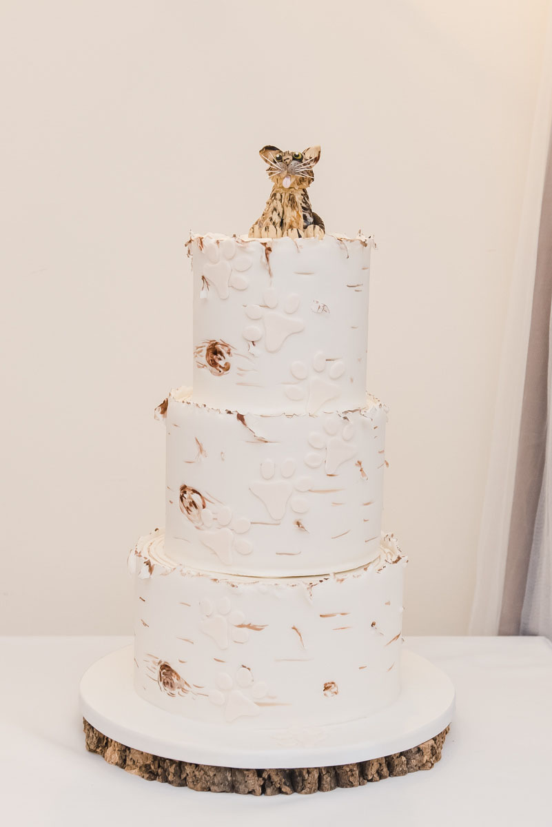 A three-tiered cream coloured wedding cake, decorated with a cat cake topper and footprints made from icing