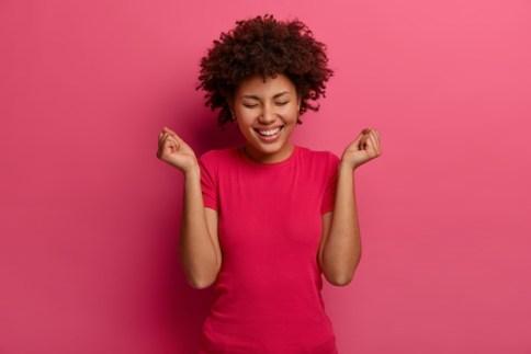 imagen-mujer-feliz-hace-gesto-bomba-puno-celebra-gran-noticia-rie-positivamente-viste-ropa-informal-rie-positivamente-posa-contra-pared-rosa-brillante-emociones-concepto-exito_273609-42537