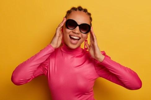 retrato-feliz-joven-piel-oscura-lleva-gafas-sol-moda-sueter-rosa-disfruta-dia-soleado-vestida-ropa-brillante-aislada-pared-amarilla-concepto-personas-moda-estilo_273609-37752