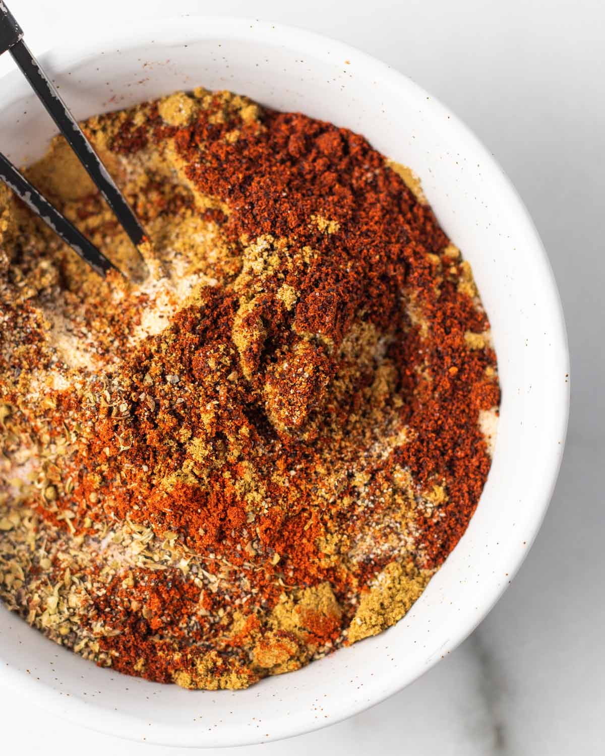 Spices mixed together in a bowl to make homemade taco seasoning.