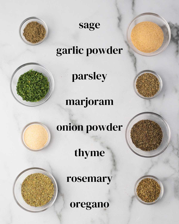 Ingredients for Italian seasoning in small bowls on a surface: sage, garlic powder, parsley, marjoram, onion powder, thyme, rosemary, and oregano.