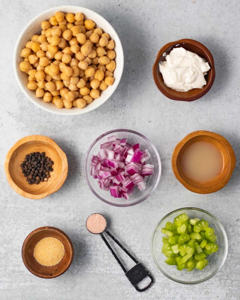 Ingredients for mashed chickpea sandwiches on a surface in small bowls or measuring spoons. Chickpeas, vegan mayo, pepper, red onion, lemon juice, garlic powder, salt and celery.