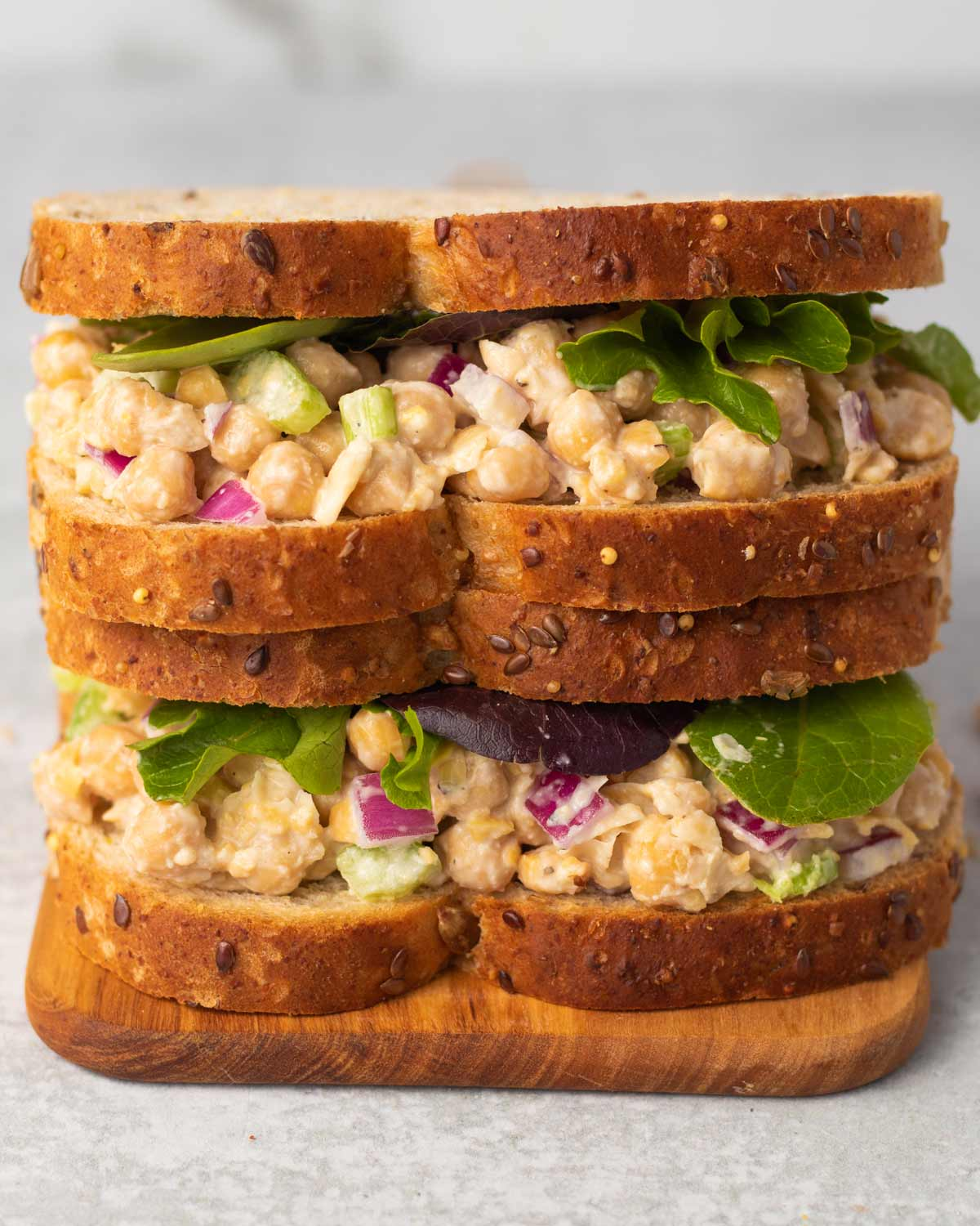 A stack of two simple chickpea salad sandwiches topped with lettuce on a wooden board.