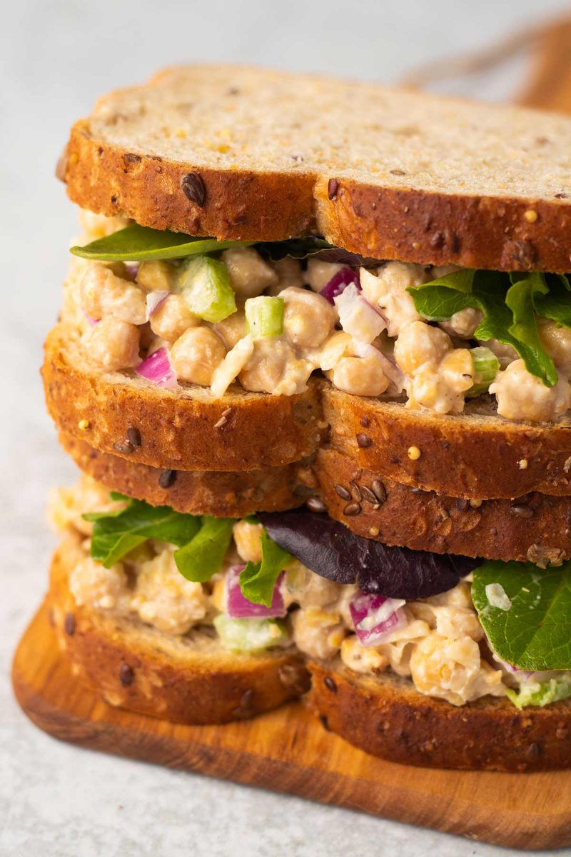 Two vegan chickpea salad sandwiches stacked on top of each other. Each sandwich is topped with some lettuce.