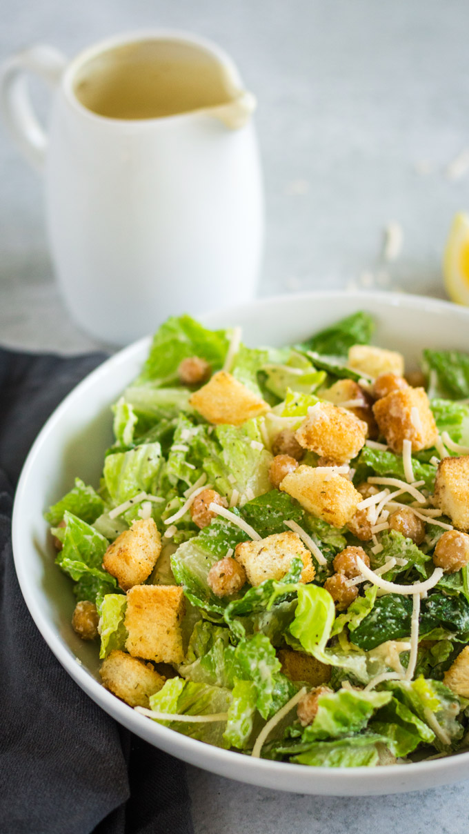 Vegan caesar salad in a white bowl, made with vegan parmesan, creamy caesar dressing, croutons and chickpeas.