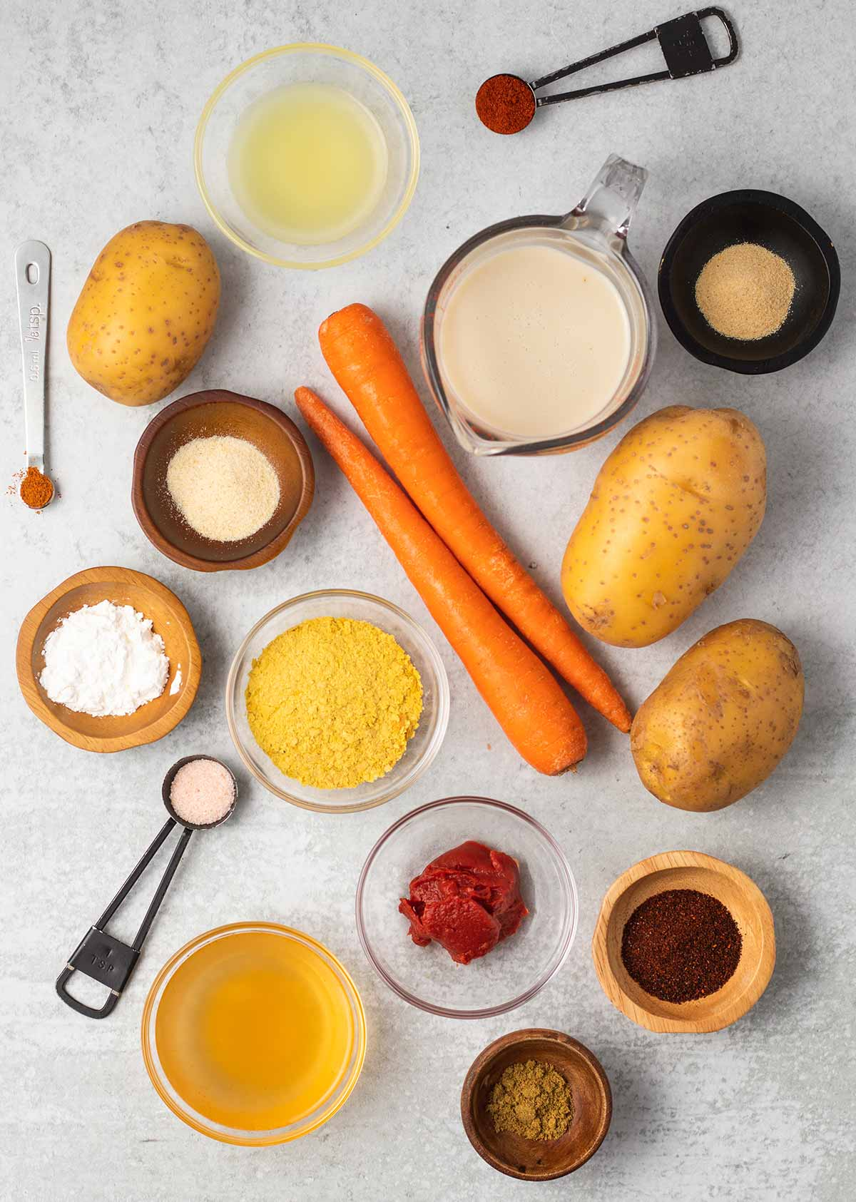Ingredients for nacho cheese sauce, some are in small bowls and measuring spoons: potatoes, carrots, garlic powder, onion powder, lime juice, cayenne pepper, chili powder, cornstarch, nutritional yeast, salt, tomato paste, and cumin.