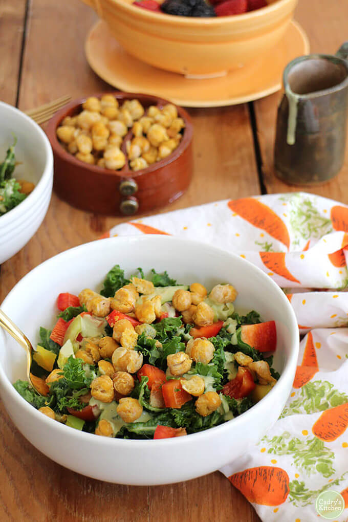 Kale salad with roasted chickpeas in a white bowl.