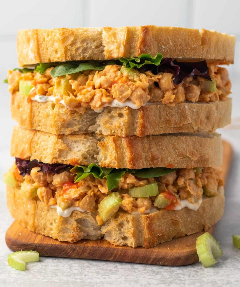 Two buffalo chickpea salad sandwiches stacked on top of each other with lettuce and vegan ranch dressing.