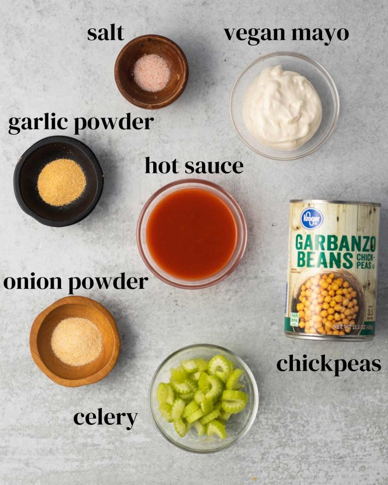 Ingredients laid out on a surface: salt, vegan mayo, garlic powder, hot sauce, onion powder, chickpeas, and chopped celery.