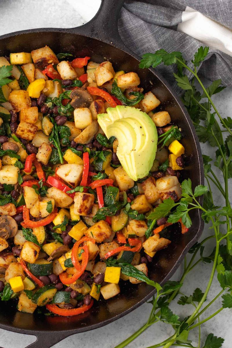 overhead of a large cast iron skillet with vegan breakfast hash of potatoes, vegetables, beans and avocado.