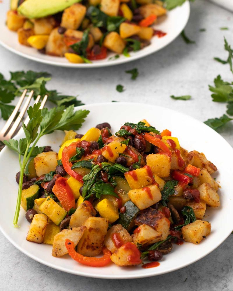 white plates with potato and vegetable breakfast hash covered in hot sauce