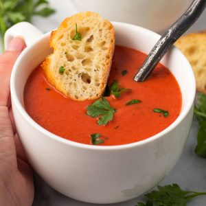 A bowl of creamy tomato soup with a baguette slice.