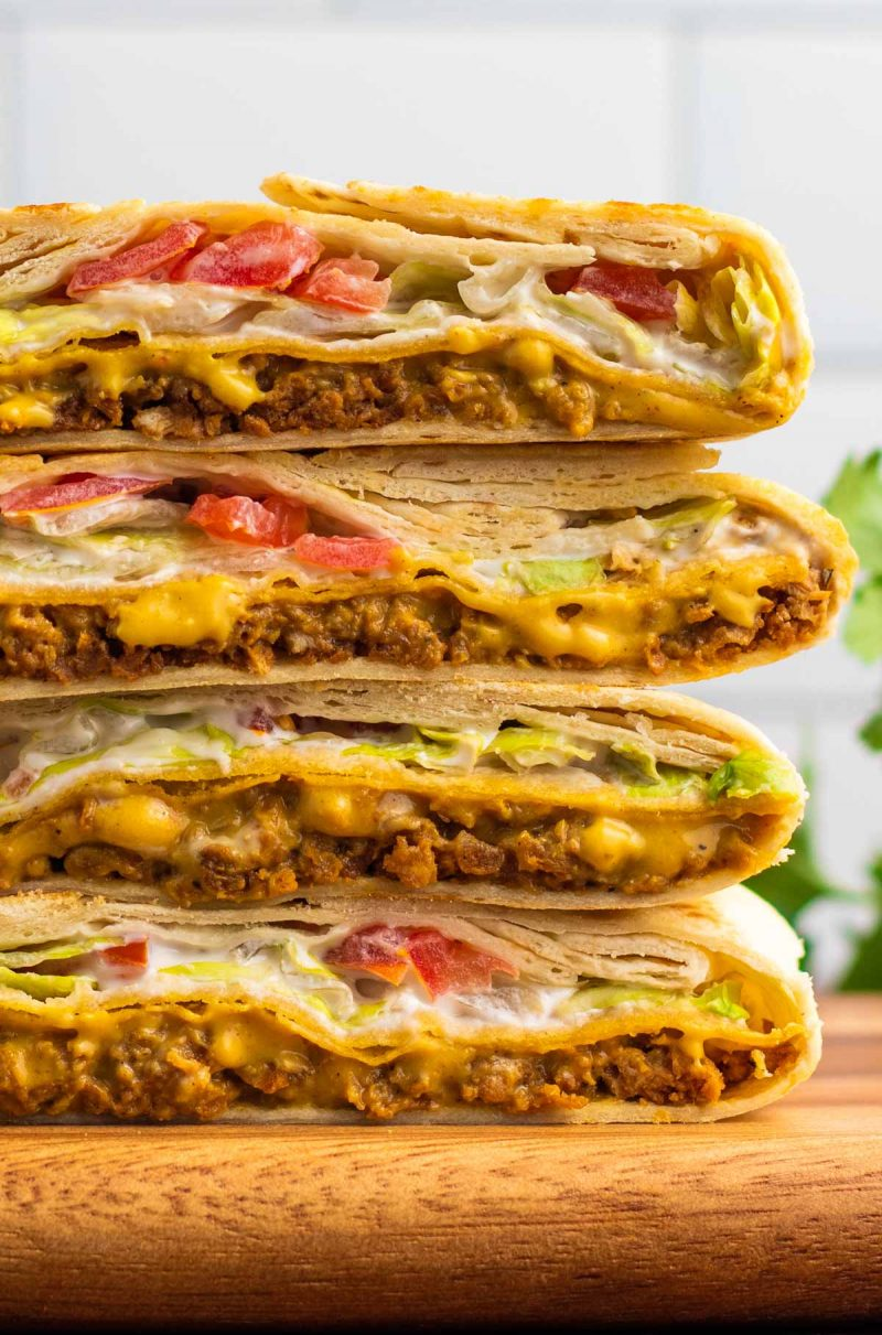 stack of vegan crunchwraps with melted cheese, ground protein and lettuce