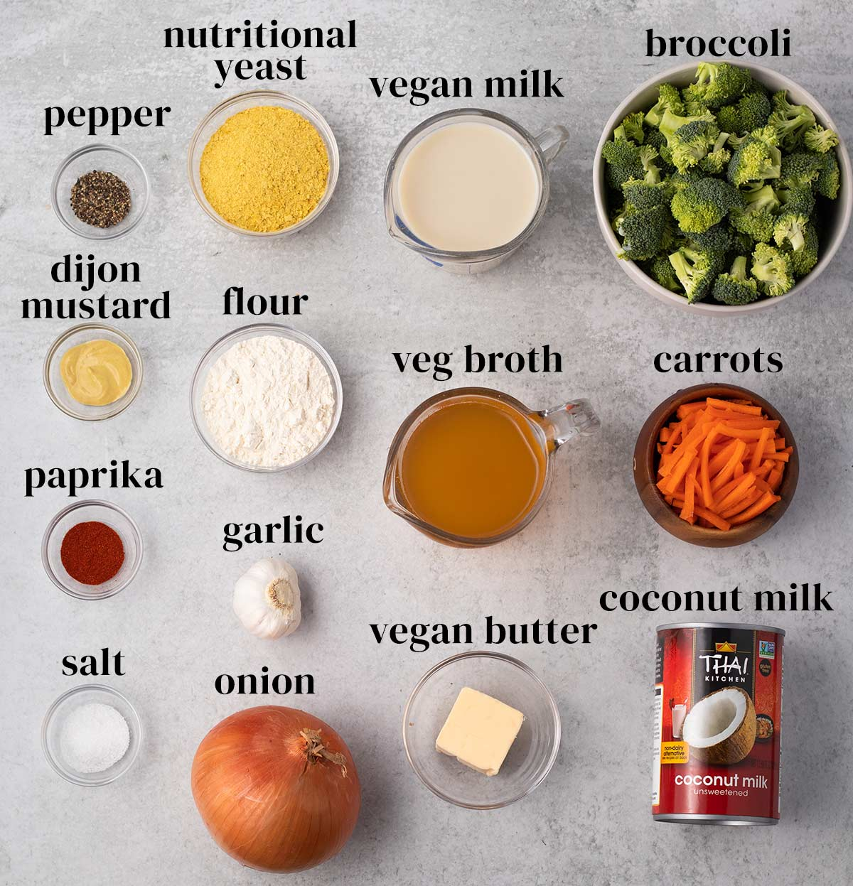 overhead of all of the ingredients to make vegan cheese broccoli soup on a grey background