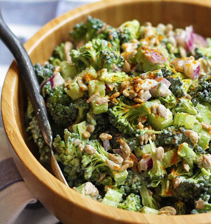 Curried vegan broccoli salad in a brown bowl with a spoon.