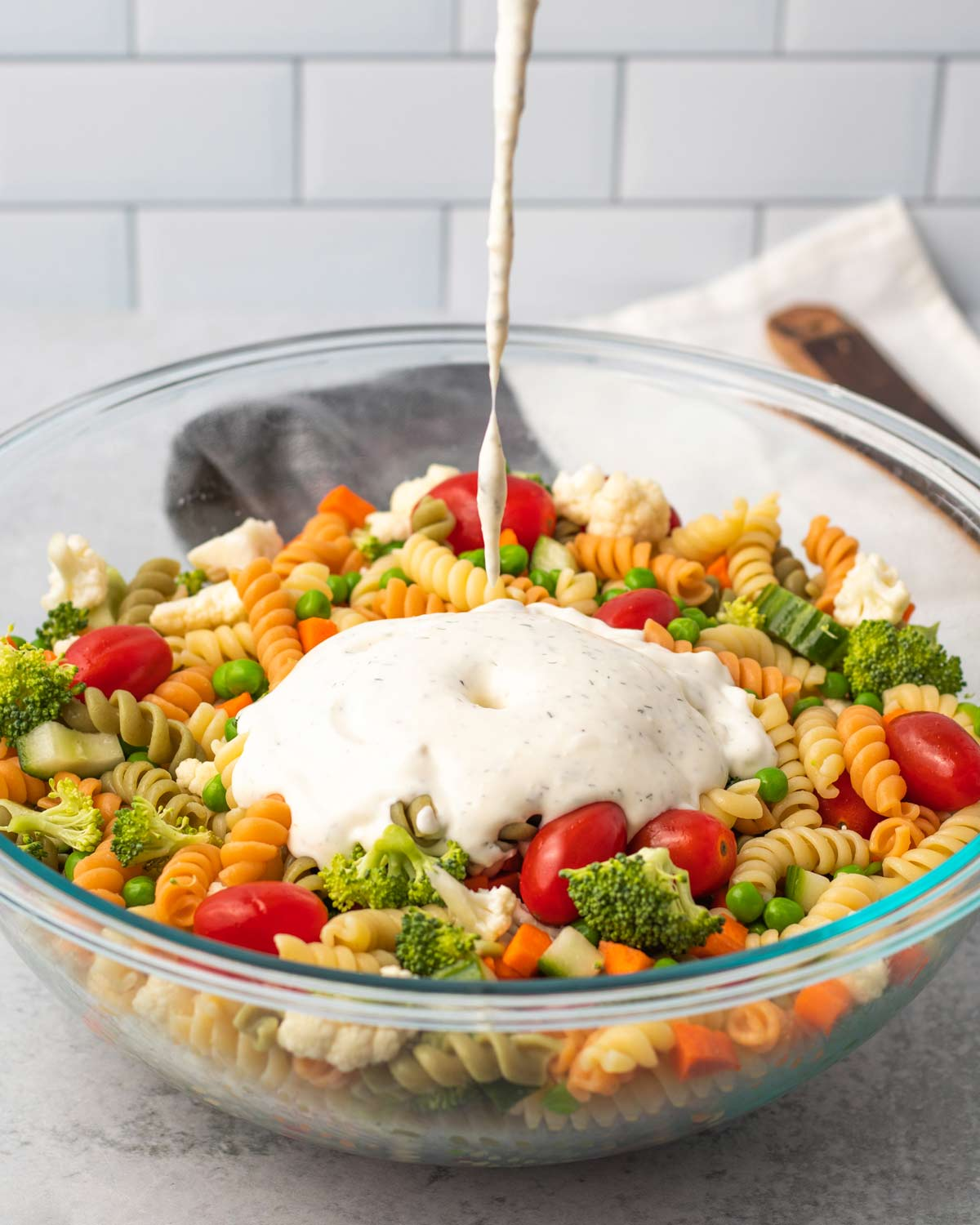 glass bowl with vegetable pasta salad with ranch dressing poured in.