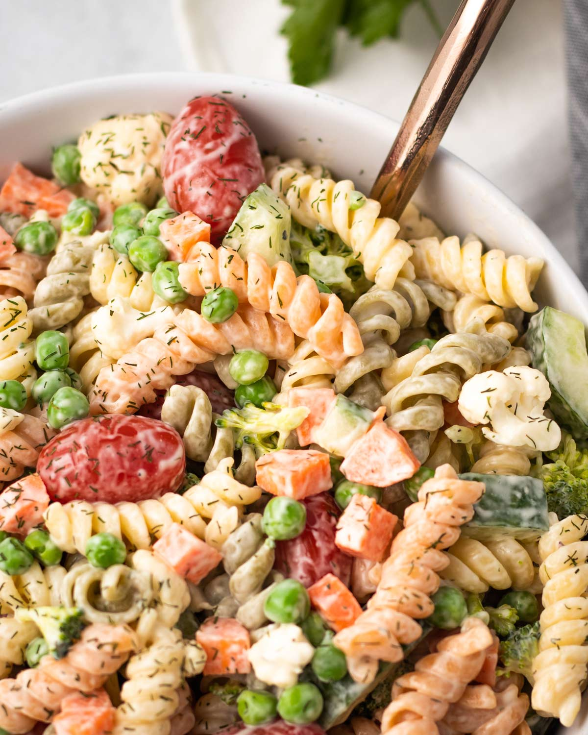 close up on vegan pasta salad with peas, carrots and rotini pasta.