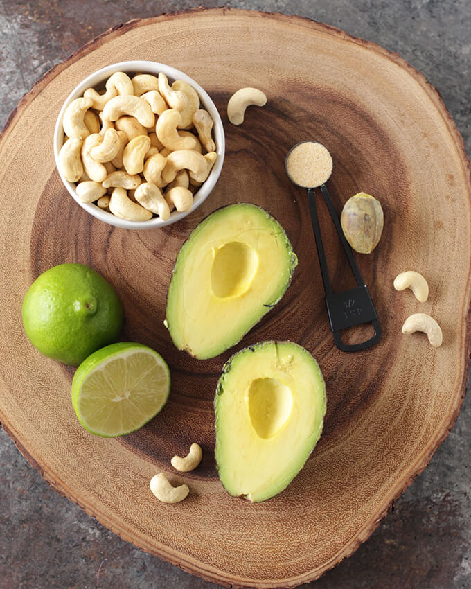 Ingredients for avocado crema on top of a circular wooden board: A small bowl of raw cashews, a lime cut in half, a halved avocado, and a 1/2 teaspoon of garlic powder.