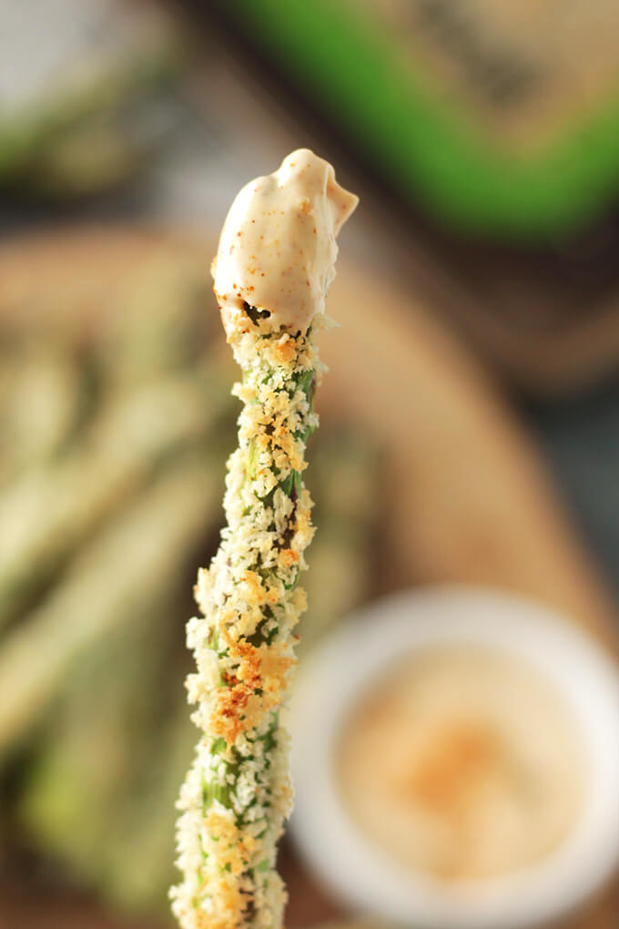 A single asparagus fry breaded in panko, dipped in a garlic aioli sauce, being held up.