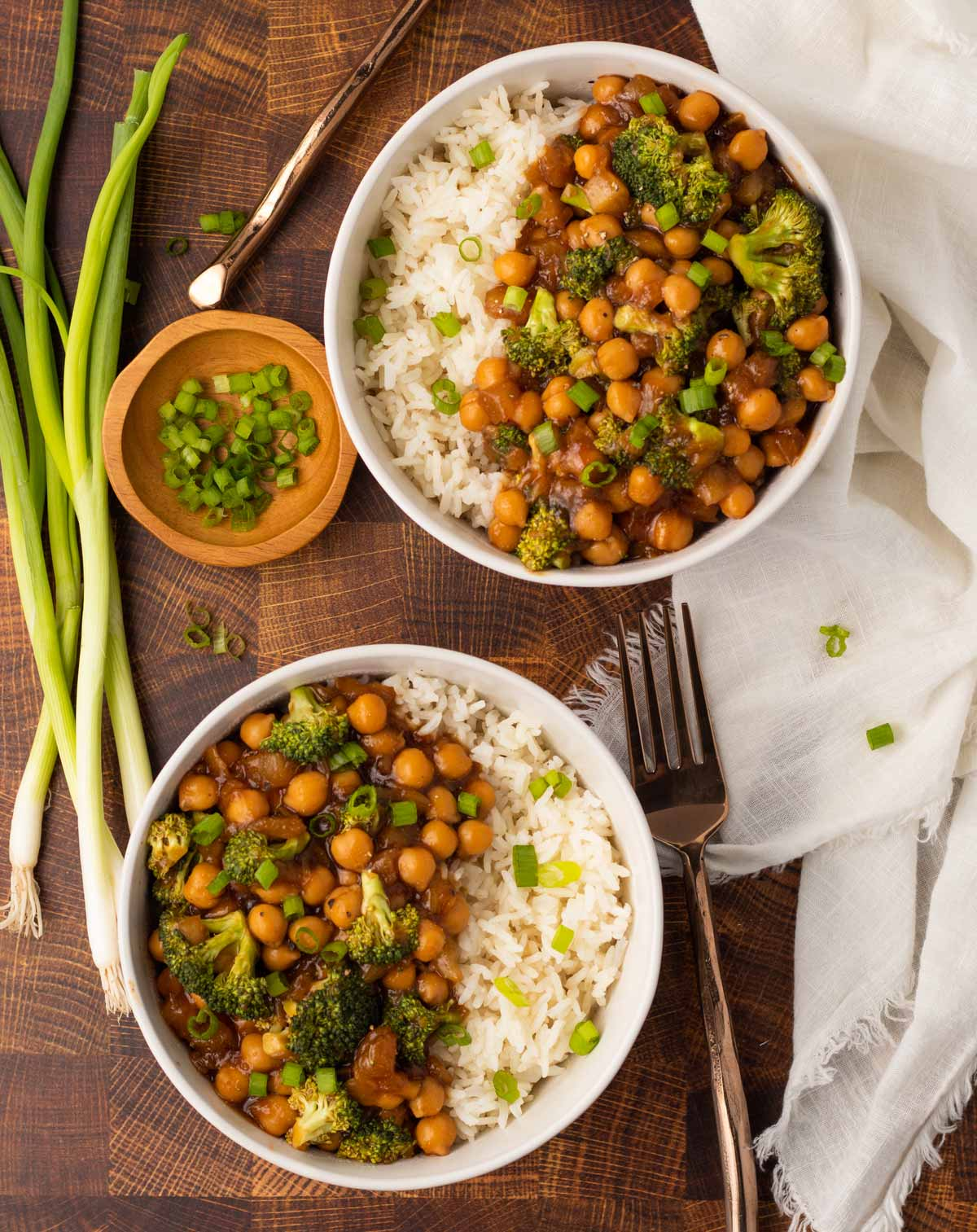 Two bowls of vegan chickpea teriyaki topped with green onions.