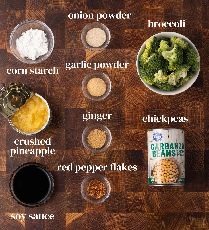 Ingredients for vegan teriyaki bowls, including chickpeas, broccoli, pineapple, soy sauce, and seasonings.