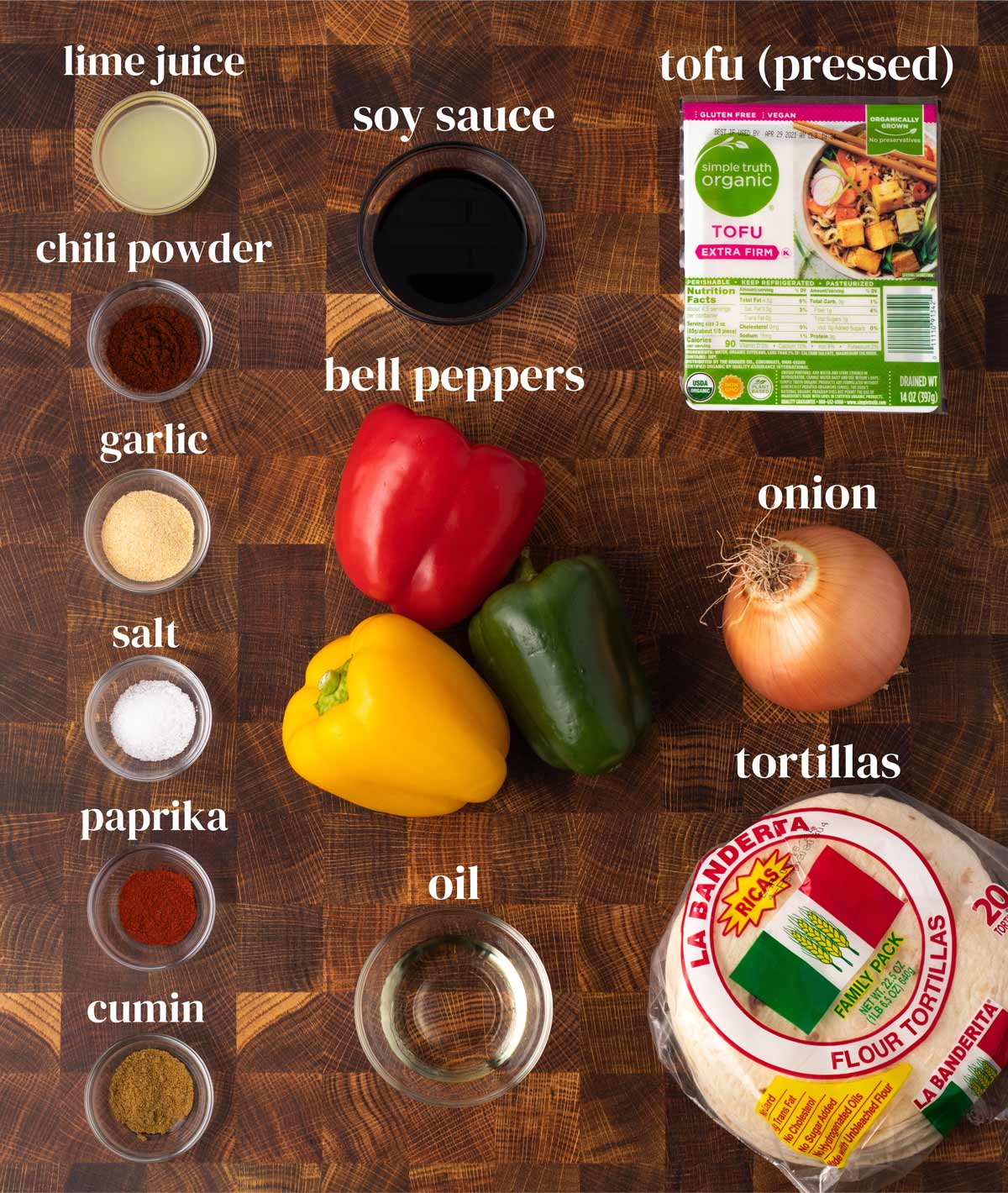 overhead of the ingredients for baked tofu fajita recipe with bell peppers and flour tortillas