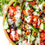 A large bowl containing vegan chopped salad with lettuces, cucumbers, tomatoes, carrots, and cashew bacon bits.
