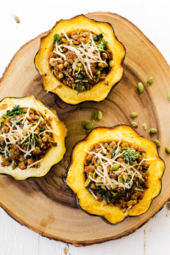 3 squash halves with a tempeh sausage and lentil filling topped with vegan parmesan.