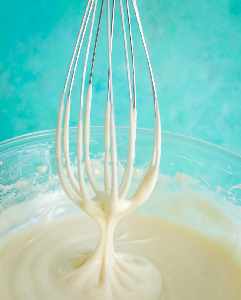 A whisk pulling out of cream cheese frosting.