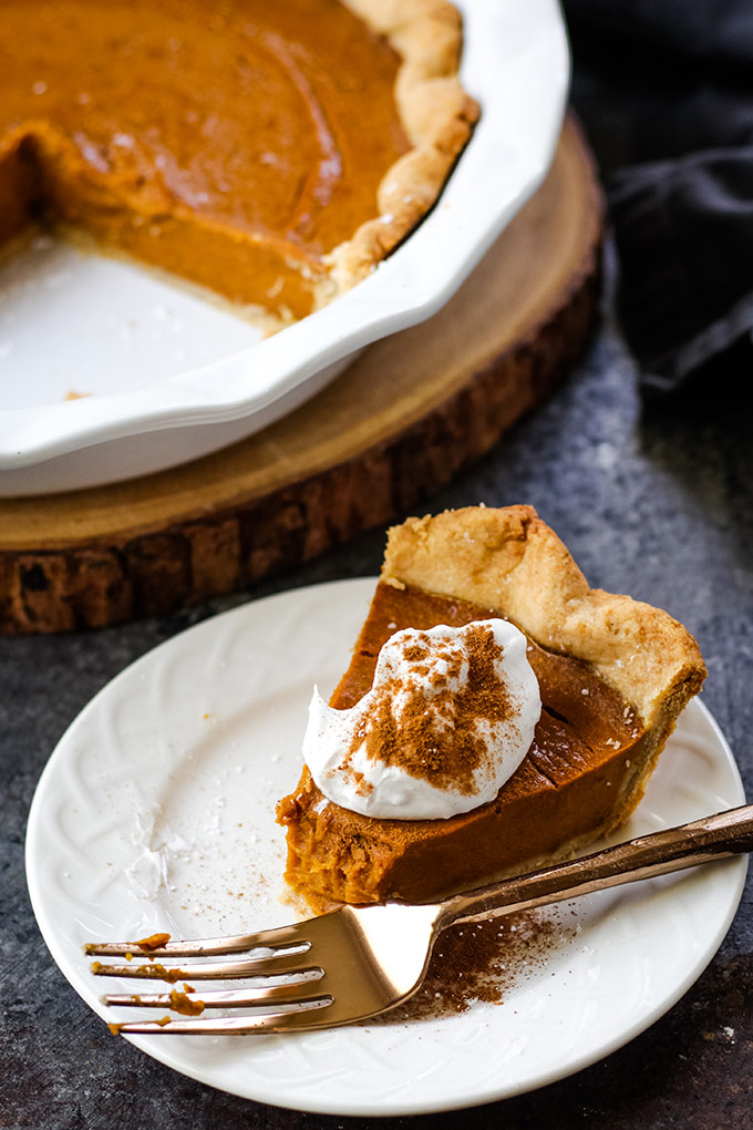 Thanksgiving pumpkin pie on a plate topped with vegan whipped cream and cinnamon.
