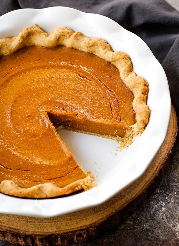 An easy vegan pumpkin pie in a white baking pan with one slice removed.