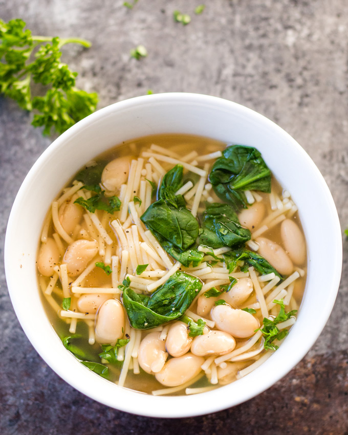Easy spinach, noodle, bean, and vegan broth sick-day soup in a white bowl on a cookie sheet background.