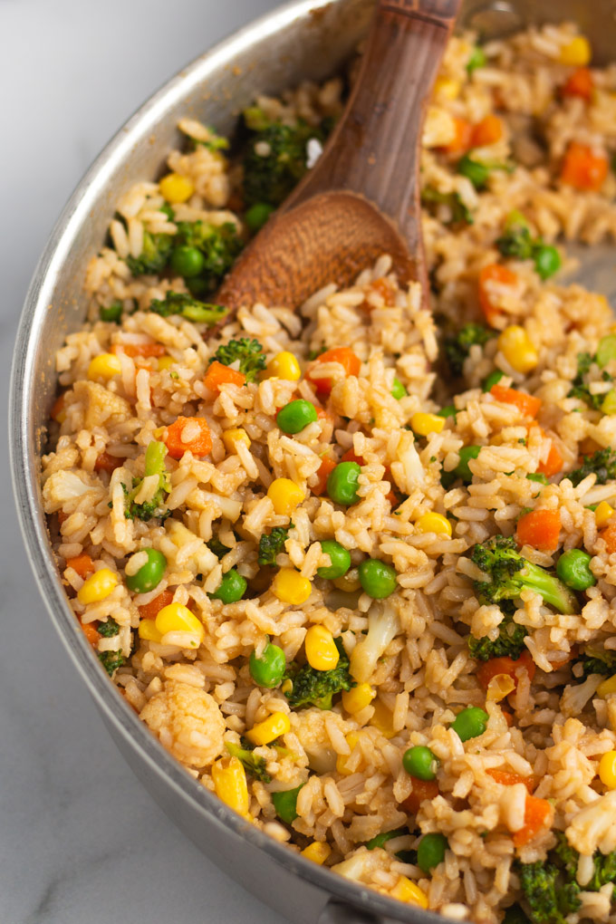 Veggie Fried Rice in a pan with peas, corn, carrots, broccoli, and cauliflower.