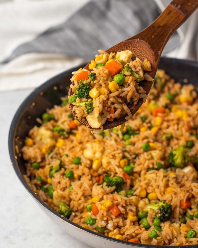 A wooden spoon with a scoop of veg fried rice over a pan.
