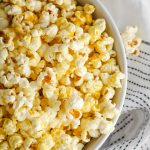 Close-up shot of cheesy vegan popcorn made with nutritional yeast in a white bowl ready to snack on!