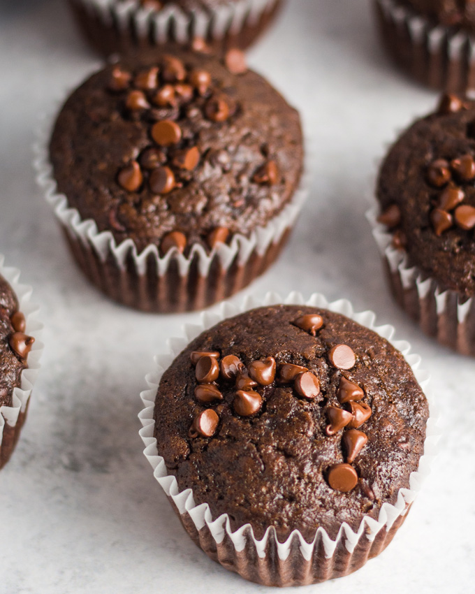 Vegan chocolate muffins in white wrappers on a cement-style surface.