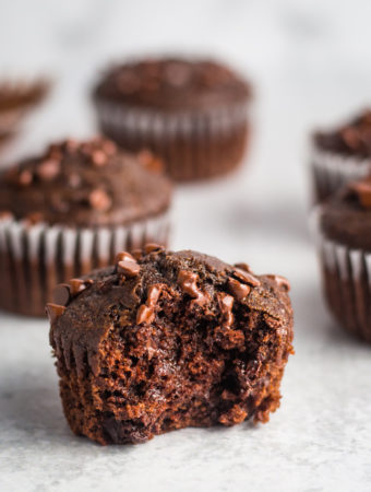 Double chocolate vegan muffins scattered out on a white surface. The muffin up front has a bite taken out.