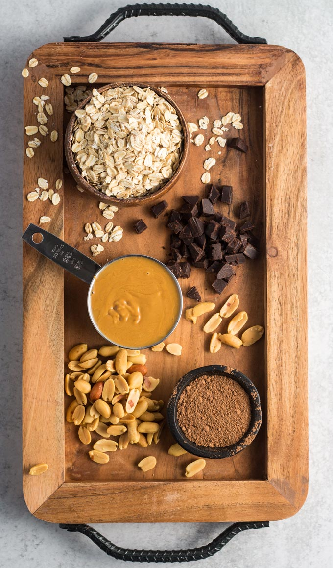 Ingredients for chooclate peant butter granola on a wooden board: oats, chocolate chunks, peanut butter, roasted peanuts, and cocoa powder.