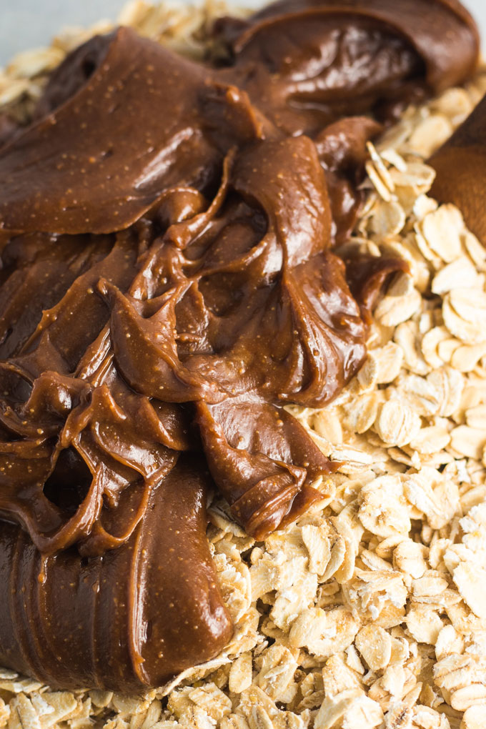 A close-up image of chocolate peanut butter sauce on top of oats ready to be mixed in to make chocolate peanut butter granola.