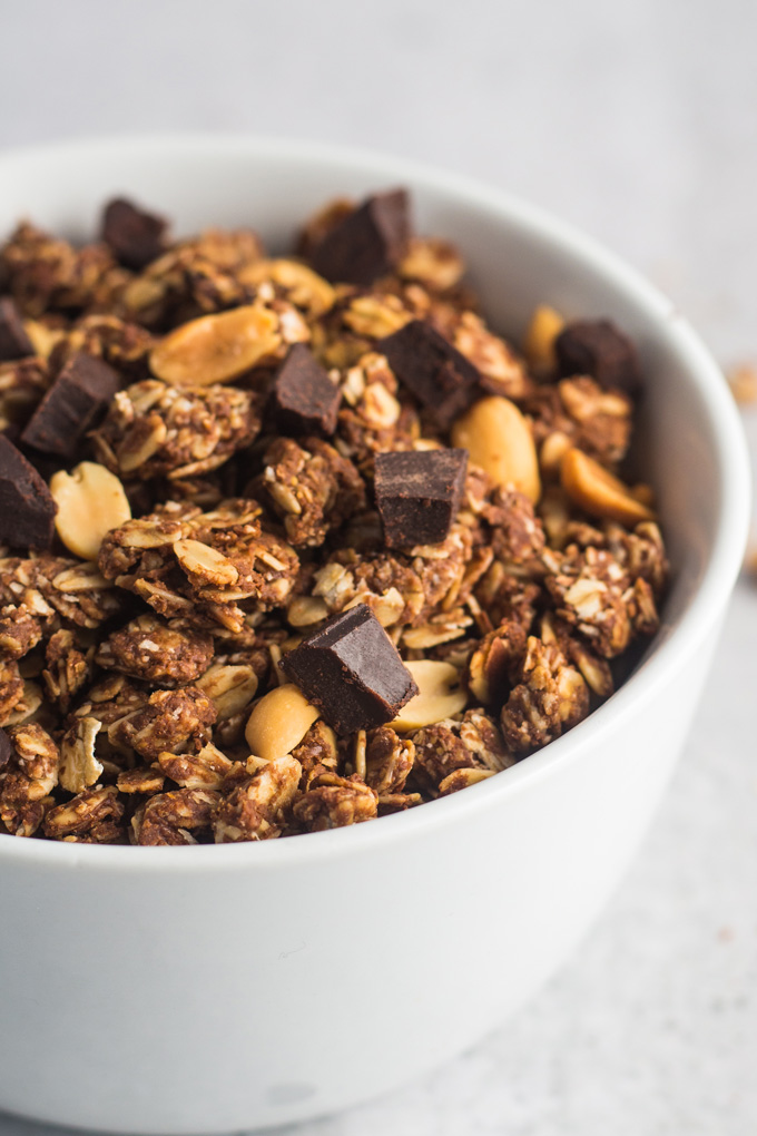Chocolate peanut butter granola topped with vegan chocolate and roasted peanuts in a white bowl on a white background.
