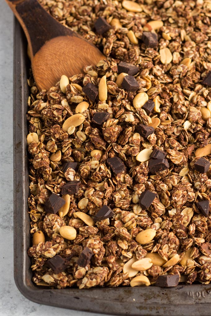 Vegan chocolate peanut butter granola on a baking sheet with a wooden spoon dug into the granola.