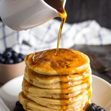 A stack of fluffy vegan pancakes being drizzled with maple syrup.