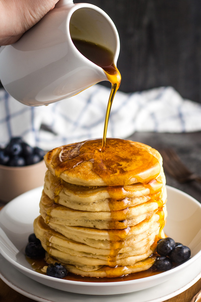 A stack of fluffy pancakes being drizzled with maple syrup.