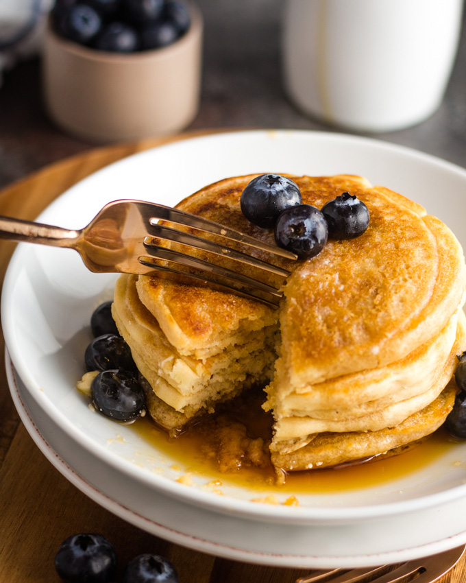 A stack of fluffy vegan pancakes on a white plate with a golden-colored fork cutting a bite off.