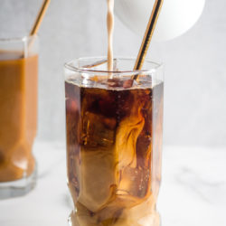 Vegan creamer being poured into a glass of vegan iced coffee.