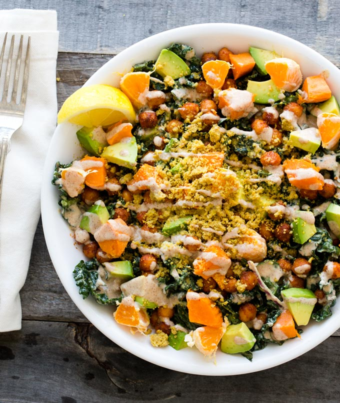 A hearty vegan salad in a white bowl containing chickpeas, avocado, kale, sweet potatoes, and more.